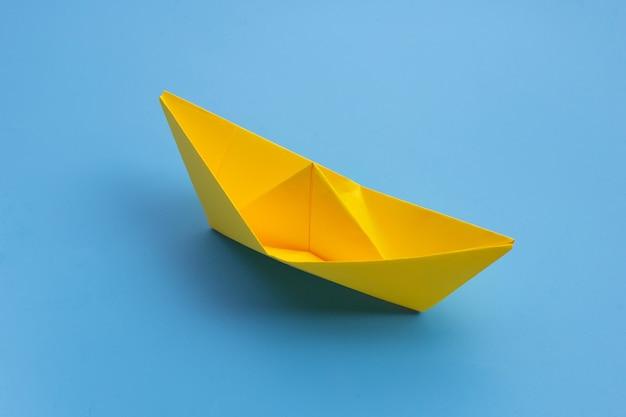 青い表面に黄色い紙のボート。コピースペース