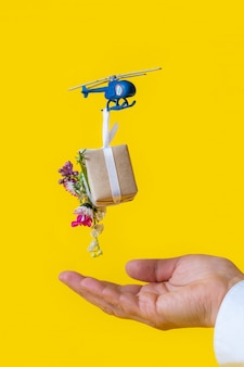 Yellow paper box gift toy delivery helicopter hand background flowers