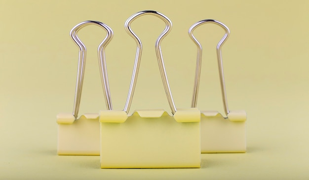 Yellow paper clip on the yellow background.business