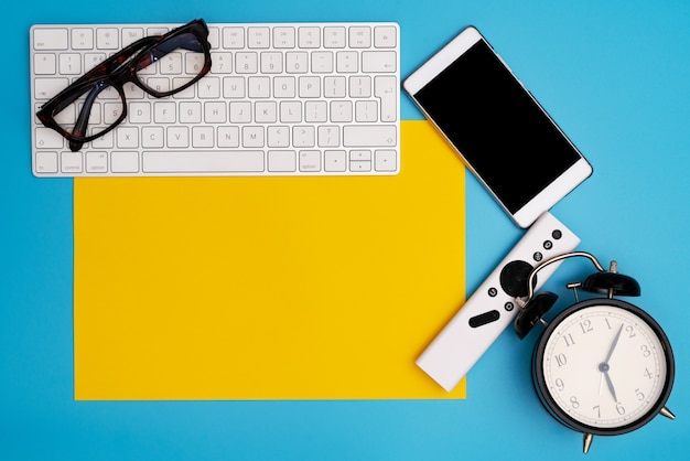Yellow paper copyspace with computer keyboard, glasses, smartphone and clock. topview, copy space