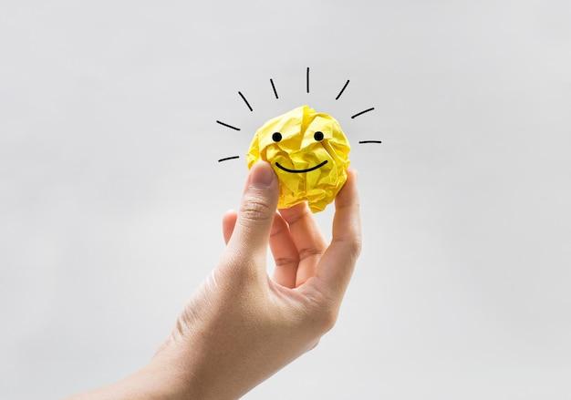 Желтый бумажный скомканный шар на руке человека с бизнес-символами