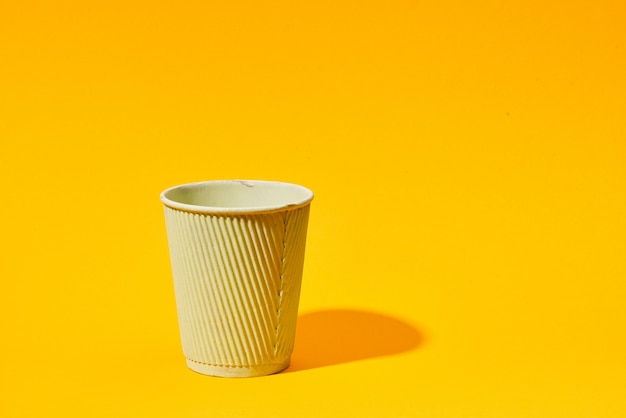Yellow paper cup standing on solid yellow