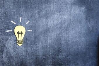 Yellow paper cutout light bulb on blank blackboard