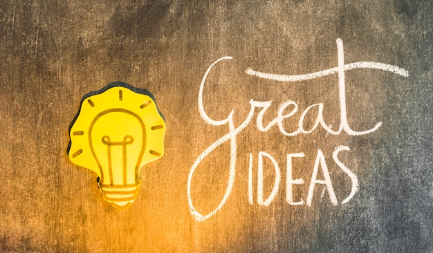 Yellow paper cutout light bulb with written text on blackboard