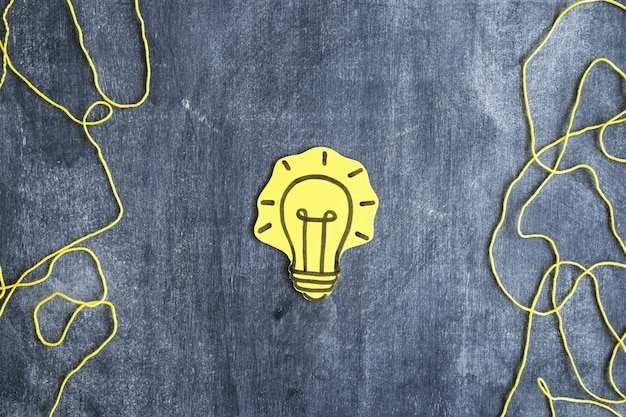 Yellow paper cutout light bulb with yarn string on blackboard
