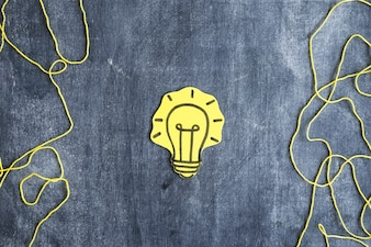 Yellow paper cutout light bulb with yarn string on blackboard