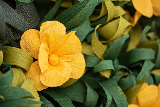 Yellow paper flowers among green leaves
