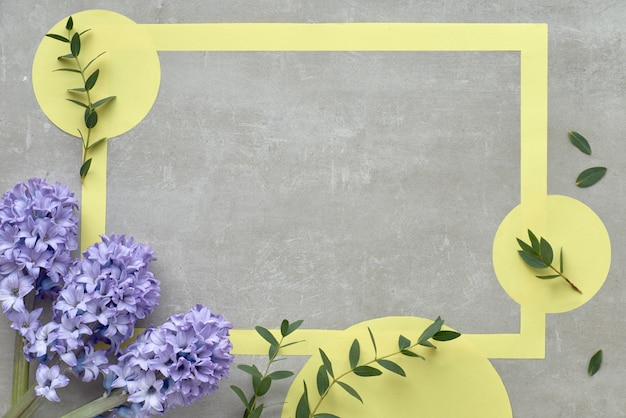 Yellow paper frame with text space decorated with blue hyacinth flowers and eucalyptus leaves