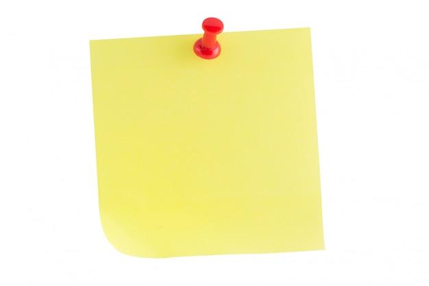 白で隔離される赤い画鋲と黄色い紙メモスティック