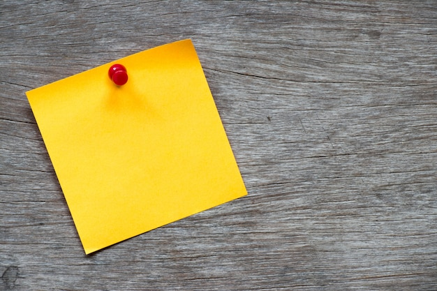 Yellow paper pin on brown wood background for memo