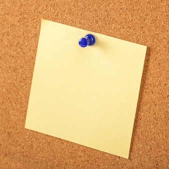Yellow paper pined with blue tack on brown cork board background.