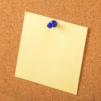 갈색 코르크 보드 배경에 파란색 압정으로 고정 된 노란 종이.