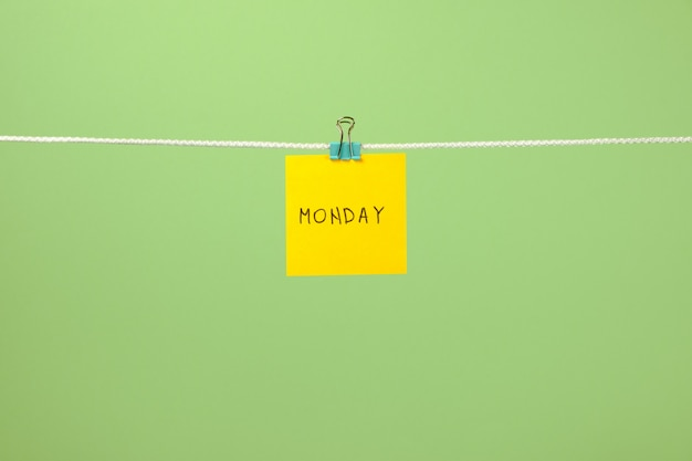 Yellow paper sheet on the string with text monday