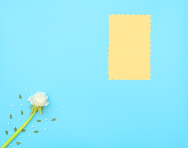 Yellow paper sheet and white flower with green leaves and white beads on blue background.