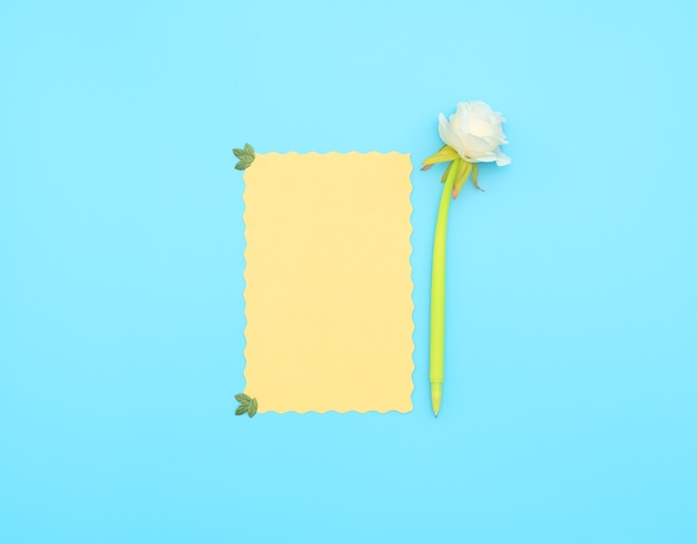 Yellow paper sheet with green pen with white flower on it on blue background.