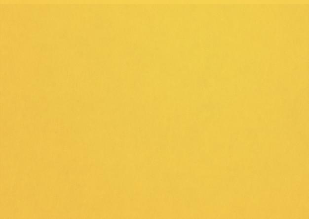 黄色い紙のテクスチャの背景。きれいな空白の壁紙