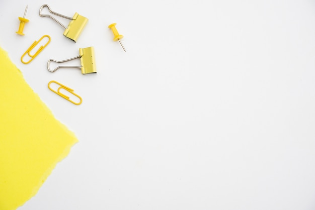 Yellow paperclip and pushpin on white background with copy space