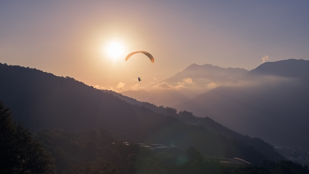 Yellow paraglider at sunset