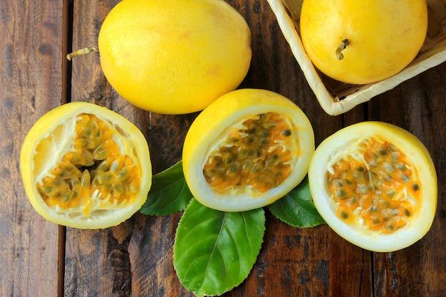 黄色の情熱果実、バスケットの中に葉があり、情熱果実が木製のテーブルの半分に切られています。