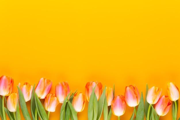 黄色のパステルは黄色の背景に花を色します。春を待っています。幸せなイースターカード。フラット横たわっていた、トップビュー。コピースペース。