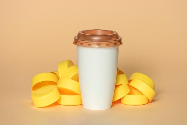Yellow pastic plugs with white coffee cup with brown lid