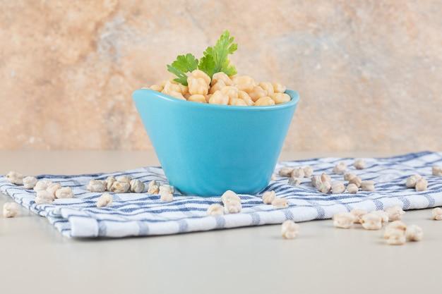 青いセラミックカップに入った黄色いエンドウ豆。