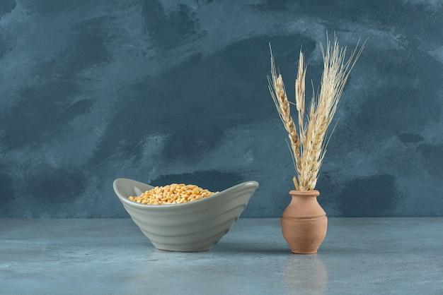 青い背景のボウルに黄色のエンドウ豆。高品質の写真
