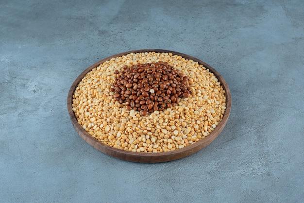 青い背景の上の木製のカップに黄色のエンドウ豆。高品質の写真