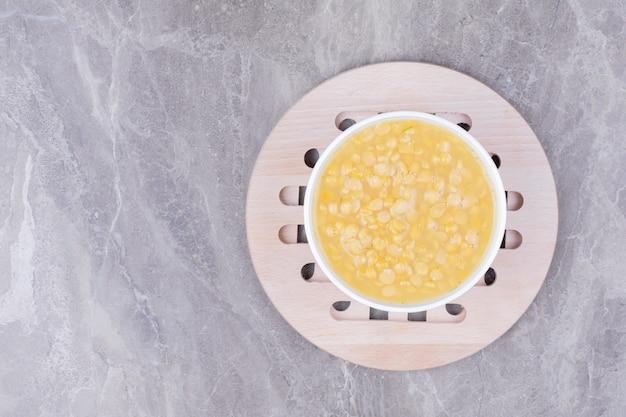 Суп из желтых гороховых бобов в белой чашке на мраморе