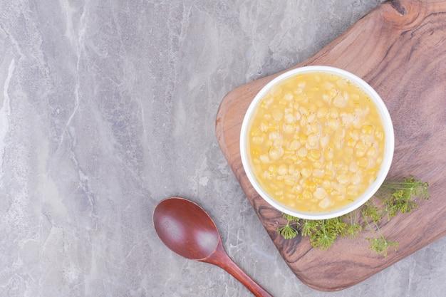 木の板の白いプレートに黄色いエンドウ豆のスープ
