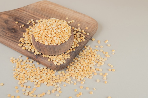 Yellow pea beans on a wooden board on concrete.