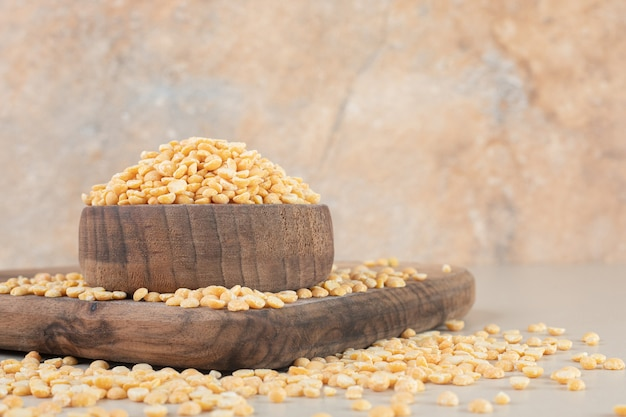 Yellow pea beans in a wooden cup on a wooden platter.