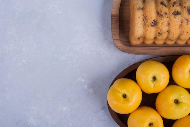 黄色の桃と木製の大皿、トップビューでロールケーキ