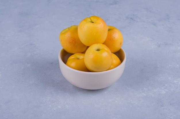 Желтые персики в белой керамической миске