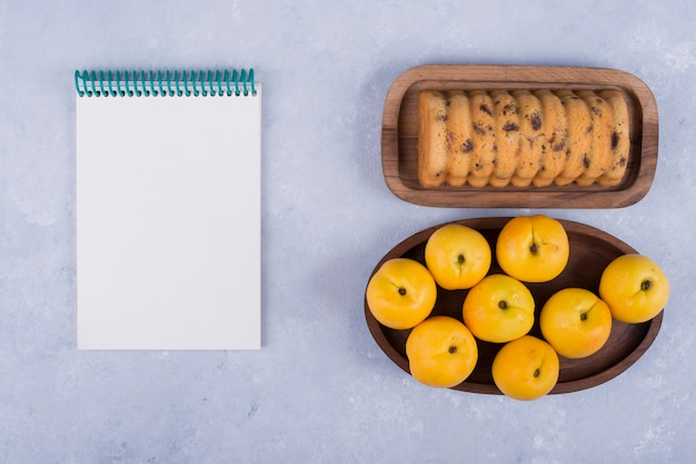 Pesche gialle e rollcake in vassoi di legno con un taccuino a parte