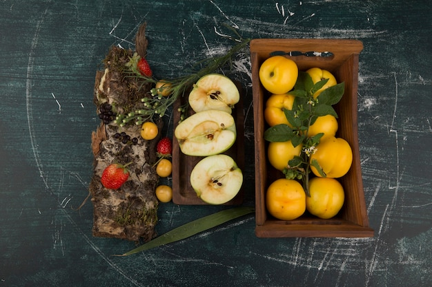Yellow peaches in a wooden tray with berries on the platter