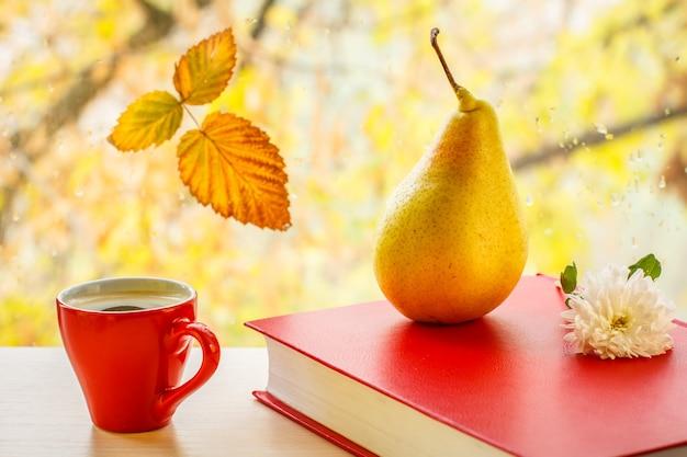 노란 배, 빨간 책, 흰 꽃, 커피 한 잔, 창문 유리에 마른 잎, 흐릿한 자연 배경에 물방울이 떨어집니다. 백그라운드에서가 나무와 창유리에 떨어진된 잎.