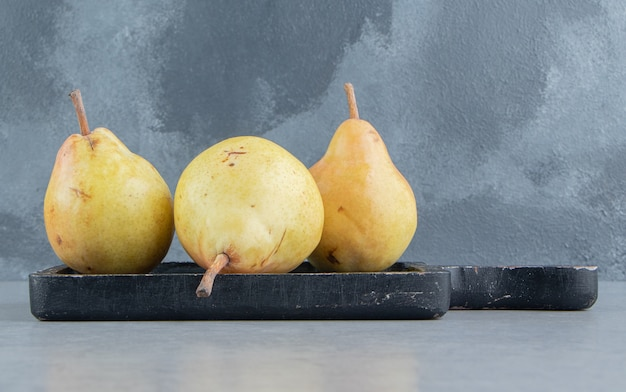 Yellow pears on a black board on marble .