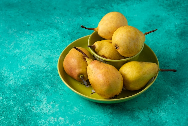Yellow pears in a green plate.