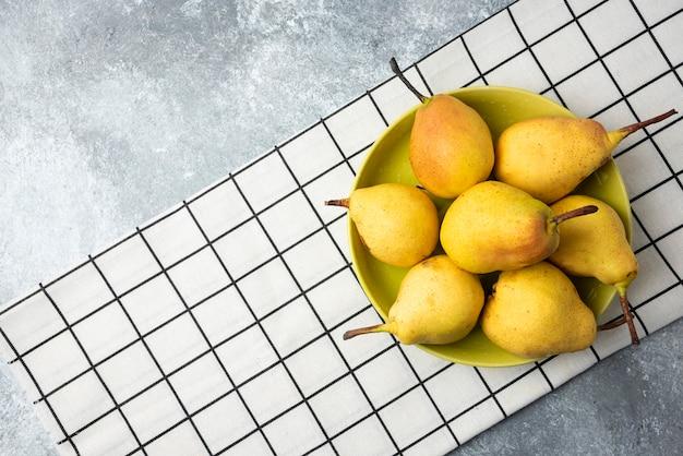 Желтые груши на клетчатом кухонном полотенце.