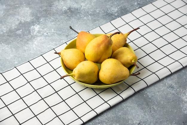 チェックのキッチンタオルに黄色の梨。