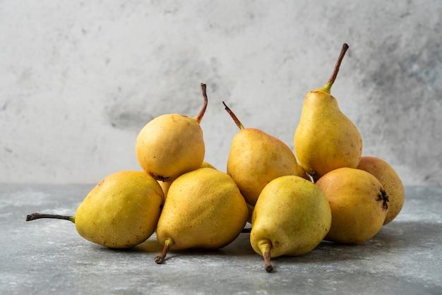Pere gialle in magazzino sulla tavola di cemento.