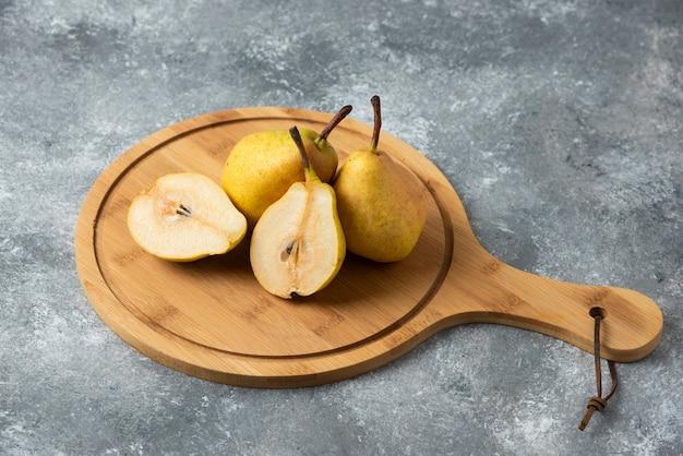 Pere gialle su un piatto di legno.