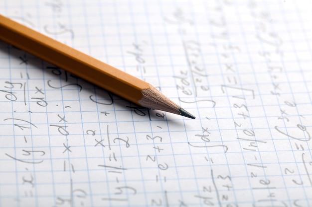 Желтый карандаш и лист бумаги с формулами
