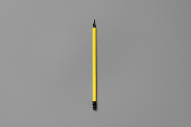 Желтый карандаш на сером фоне вид сверху