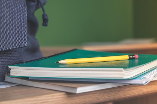 Желтый карандаш на стопку учебного ноутбука на деревянный стол и синий рюкзак