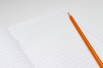 Yellow pencil on the background of a white lined sheet of notebook
