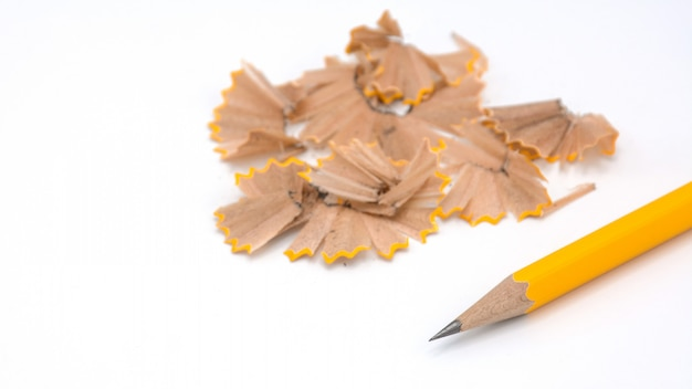 Yellow pencil placed and the sharpener chips on white background