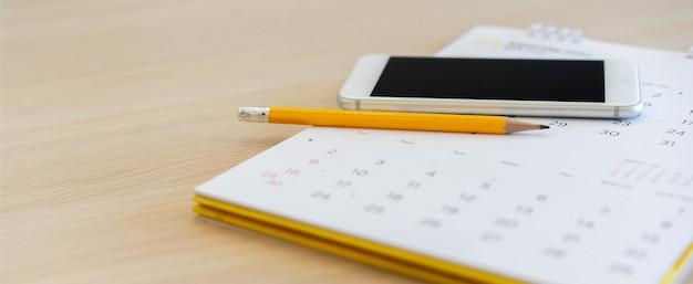 予定コンセプトのホームオフィステーブルでカレンダーにスマートフォンで黄色の鉛筆