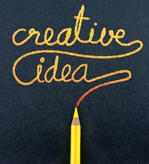 Желтый карандаш написать творческое слово идеи на бумаге черного ремесла